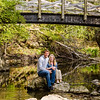 Engagement photo of couple sitting on a rock in the river