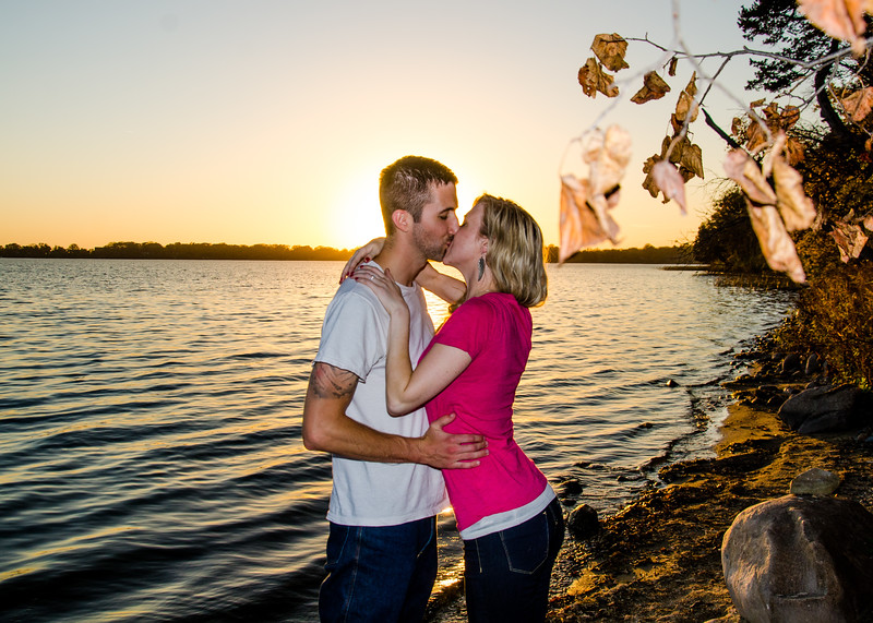 engagement photo of couple kissing on front of lake