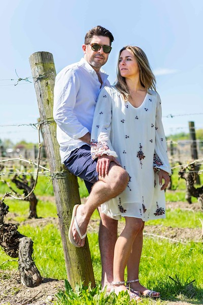 engaged couple standing in a vineyard