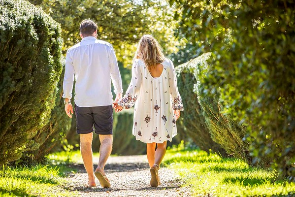 engaged couple walking away hand in hand