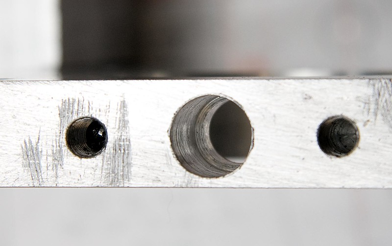 The hole for the locking pin, showing the ledge that the spring compresses against