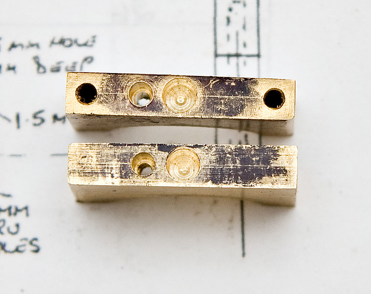 The top halves of the eccentric straps with the connecting rod holes in the centre and the oil holes offset slightly.
