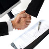 Businesswoman and businessman shaking hands with signed contract on background