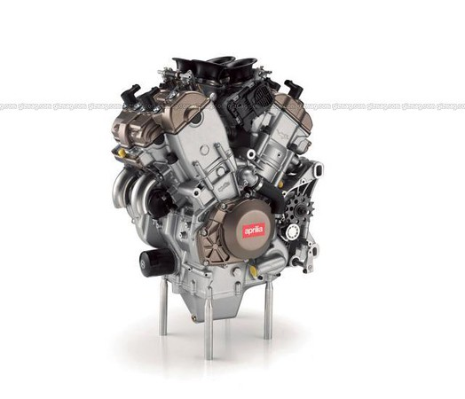 October 8, 2007 Aprilia tell us their much-anticipated V4 engine is currently undergoing durability testing in four states of tune – from a huge 185 horsepower up to an eye-watering 220 horsepower. Which one will we see in the road-going superbike they're building?<br /> <br /> With many MotoGP bikes now running V4 engines due to their compact size and broad power spread, the worldwide roadbike market is crying out for a V4 sportsbike they can play with themselves.<br /> <br /> Honda, as usual, are proceeding at a very conservative pace. Although V4 and V5 1000cc engine patents have been taken out, Honda tell us not to expect them to hit the streets for another 2-3 years, at which point the new engine will be a platform for a number of sports and touring models, presumably finally replacing the popular but unspectacular VFR800 and the inline-four cylinder CBR1100XX Blackbird.<br /> <br /> Aprilia, however, are proceeding at a rate of knots with their first ever first 4-cylinder engine and intends to race its 1000cc engine as early as 2008. Aprilia Australia tells us there's currently four versions of the V4 undergoing longevity dyno testing, testing how reliable and durable the engine will be in various states of tune. The lowest state of tune is making a very hairy-chested 185 horsepower, putting it right on par with the big 4 Japanese sportsbikes. The highest state of tune is making a blistering 220hp, which would topple the MV Agusta 312 and blow away every other production bike on the planet. Suffice to say, this engine will be a monster.<br /> <br /> The company tells us that no decision has yet been made on whether to race the 1000cc model in World Superbikes or whether a scaled-down 800cc model may be built for the company to take to the MotoGP stage.<br /> <br /> If the company go to World Superbikes, things will be very interesting – as while Ducati and the Japanese brands have dominated the competition in the last decade or so, we could be about to see a s