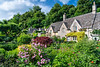 Alarge stone home with flower gardens in the Cotswold village of Bibery, Gloucestershire, England, Europe.