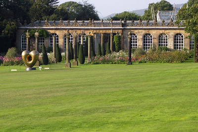 The Conservatory or Orangery, moved in 1760 from its previous location at the Maze. Built by the first duke to house his Mediterranean orange and lemon trees, but now containg camellias and mimosas. A rose garden is in front of it.