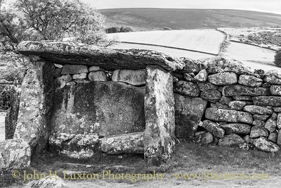 The Judge's Chair at the entrance to Dunnabridge Pound.  Dunnabridge Pound is a large enclosure of unknown date situated almost dead centre of the high moorland of Dartmoor. When it was created is not known – it has been variously described as a 'late prehistoric pound' and a 'mediæval stock enclosure'.  An overall analysis suggests that the enclosure may have been originally a Bronze Age enclosed settlement similar to that at Grimspound, but rebuilt over later ages, to serving as a cattle pound from the Middle Ages into the modern period. The visible structure of Dunnabridge Pound appears to be mediæval though with later rebuilding. It consists of a drystone wall, built of large rough granite blocks in roughly circular plan. The entrance, facing the road, is divided by granite monolith into a wider and narrower opening.  This pound is very well preserved, as it has been maintained over centuries. Just inside the Pound's entrance near the road is a structure known as The Judge's Chair, which may have been installed here as recently as the Georgian period. This is a large stone seat, integral with the wall, with a large granite canopy above providing shelter.  (Information from WikiShire)