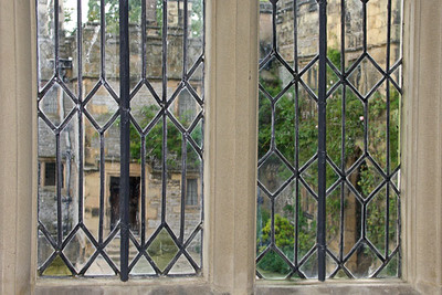 View of courtyard from interior of Haddon Hall. Most if not all of the rooms have windows peering into the courtyard.  The diamond shapes within the glasses are irregular in order to capture the sun's rays at different angles, so that rooms are always well-lit in the daytime.