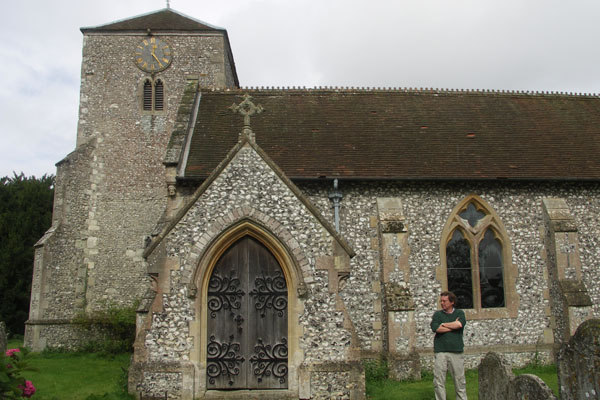 """Phil in front of Manydown church on the Manydown estate. The wealthy Bigg family owned the large Manydown estate (the mansion was torn down in 1965). Harris Bigg-Wither, son of the Biggs, proposed to Jane Austen in 1802 when she was 26, and was buried at the church here. Jane regretted accepting his proposal, broke it off the next morning, and abruptly fled Manydown with Cassandra. She may have initially accepted him because of the financial security that he could provide for her and her family (""""And of of all this I could have been mistress"""" Elizabeth Bennett on Pemberley, after rejecting Darcy's proposal in Pride and Prejudice)."""