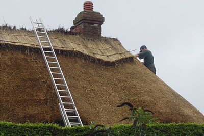 Repairing a thatched roof. Apparently there are not a lot of thatched cottages anymore because fire insurance is so expensive!
