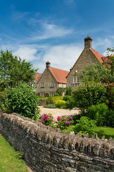 A modern stone house and fence in the village of Lacock, Wiltshire, England.