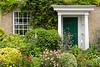 A door, garden and entrance yard with flowers in Salisbury, Wiltshire, England, Europe.