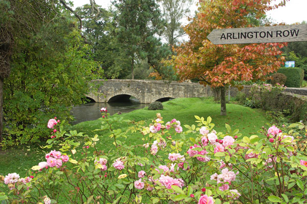 In Bibury, a sign points over the River Coln and water meadow to a picturesque  row of weaver's houses called Arlington Row, in the adjacent tiny village of Arlington, named after the Arlington family with settled and owned the town.
