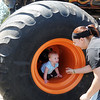 A small child crawls inside a giant wheel on Bruce Kunkel's Sudden Death monster truck during a picnic at Meadowlake Park Sunday, April 21, 2013. (Staff Photo by BONNIE VCULEK)