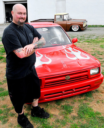 Jim Stuart stands in front of two of his custom trucks at his shop Sunday. (Staff Photo by BILLY HEFTON)