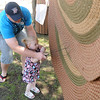 John Bailey and his daughter, Felicity, learn how to beat a rug the old-fashion way during the Cherokee Strip Regional Heritage Center family fun day in Humphrey Heritage Village Saturday, April 13, 2013. (Staff Photo by BONNIE VCULEK)
