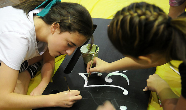 Waller Middle School Advanced Art design team members (from left) Kendall Carpenter and Alana Brehm paint music symbols on the front panel of a piano during Pam Gilbreath's art project at the Cherokee Strip Conference Center Friday, April 26, 2013. The project, sponsored by Main Street Enid, is part of the upcoming Tri-State Music Festival. (Staff Photo by BONNIE VCULEK)
