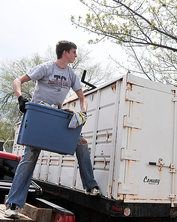 Trevor Field from the NOC-Enid FCA sets to toss a container of debris from a house being remodeled by Forgotten Ministries into a dumpster Saturday. Central Christian Church is hosting youths from around the state as they work on mission projects. (Staff Photo by BILLY HEFTON)
