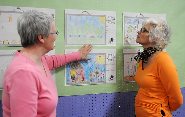 Paula Nightengale (left) and Jelka Shearon discuss the artistic talents of Eisenhower Elementary School K-2nd grade students as they view the Emerging Artist Gallery display at Park Avenue Thrift Tuesday, April 16, 2013. A reception honoring the students will be this Saturday at Park Avenue Thrift. (Staff Photo by BONNIE VCULEK)