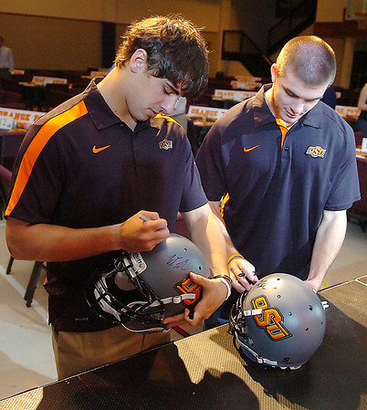 Oklahoma State quarterbacks, Clint Chelf and J.W. Walsh autograph helmets prior to the Fellowship of Christian Athletes dinner Monday at Emmanuel Baptist Church. (Staff Photo by BILLY HEFTON)