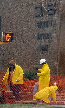 As heavy rain and sleet fall, workers prepare a sidewalk area for brick pavers at the Security National Bank drive-thru branch on the corner of Maine and Independence Wednesday, April 03, 2013. (Staff Photo by BONNIE VCULEK)