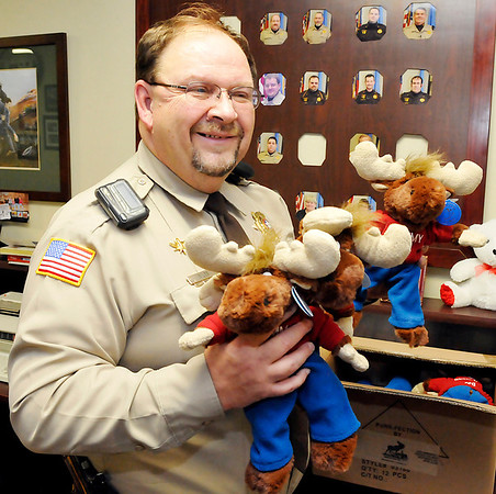 Garfield County Sheriff, Jerry Niles, holds some of the Tommy the Moose animals donated to the sheriff's department by the local Moose Lodge. The animals will be given to children involved in unfortunate situations. (Staff Photo by BILLY HEFTON)