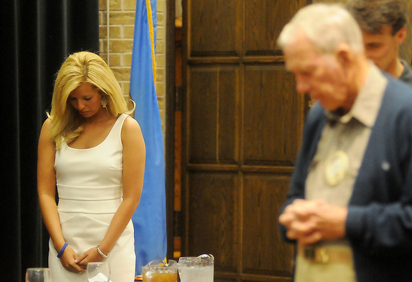 Aly Akers (left) bows for a word of prayer with Enid Noon AMBUCS members Friday, April 5, 2013. Akers, a senior at Oklahoma State University and feature twirler for the OSU Cowboy Marching Band, will compete in the Miss Oklahoma pageant later this year. (Staff Photo by BONNIE VCULEK)