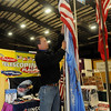 Paul Olsen, from Uncommon USA Inc., raises one of the telescoping flagpoles during the Enid Home Show at the Chisholm Trail Coliseum Friday, April 26, 2013. The annual show continues through Sunday. (Staff Photo by BONNIE VCULEK)