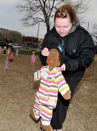 Christina Marple places a wooden child in place on the Garfield County Courthouse lawn Monday by the Garfield Child Advocacy Council. Each of the 93 wooden children represents an abused and/or neglected child in Garfield County. (Staff Photo by BILLY HEFTON)