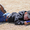 "Brand West, from Perry, plays ""Jet Pack Joy Ride"" on the Chisholm High School football field as he waits for his sister to compete during the Boys and Girls Invitation Track and Field Meet Friday, April 12, 2013. (Staff Photo by BONNIE VCULEK)"