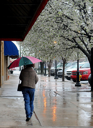 A woman uses an umbrella and business awnings to shield herself from the falling rain and sleet on Grand Avenue Wednesday, April 03, 2013. (Staff Photo by BONNIE VCULEK)