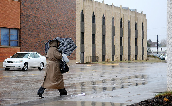 Heavy rain and sleet fall as a woman walks to Central National Bank Wednesday, April 03, 2013. (Staff Photo by BONNIE VCULEK)