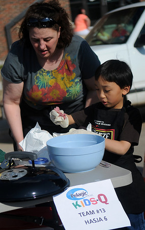 Violet Hassler watches as her son, Jake, prepares his hamburgers for the Pelagic Tank Kids-Q during the 8th annual Roberts Ranch Smokin' Red Dirt Barbeque outside Convention Hall Friday, April 19, 2013. (Staff Photo by BONNIE VCULEK)