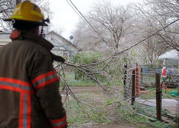 After an ice covered tree branch falls on an O.G.&E. service line at 811 E. 2nd Pine, an Enid firefighter waits patiently in the cold for a line crew to arrive Wednesday, April 10, 2013. (Staff Photo by BONNIE VCULEK)