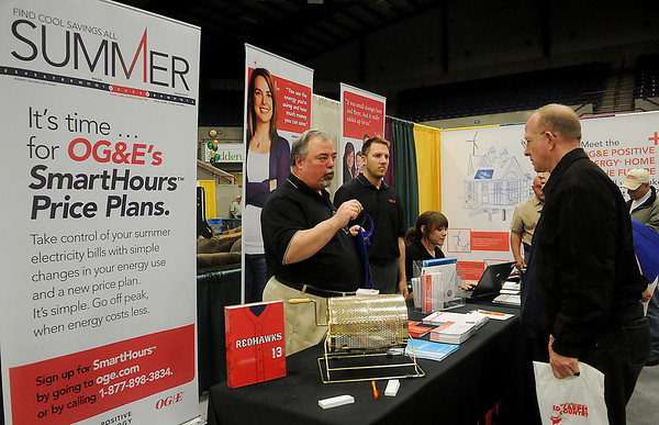 Mike Newcomb, O.G.& E. Smart Grid Supervisor from Oklahoma City, explains the Smart Hours Price Plans to Howard and Linda Deunk (right) during the Enid Home Show at the Chisholm Trail Coliseum Saturday, April 27, 2013. (Staff Photo by BONNIE VCULEK)
