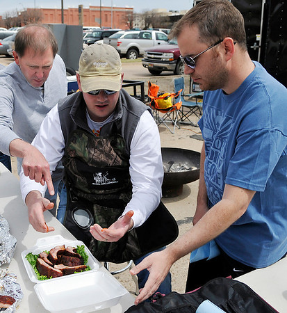 Members of the Can't Beat Our Meat barbeque team discuss the proper placement of ribs for presentation Saturday during the Smokin' Red Dirt Barbeque contest in downtown Enid. (Staff Photo by BILLY HEFTON)