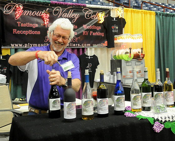 Dennis Flaming, with Plymouth Valley Cellars, opens a bottle of his wine for guests during the Enid Home Show at the Chisholm Trail Coliseum Friday, April 26, 2013. (Staff Photo by BONNIE VCULEK)