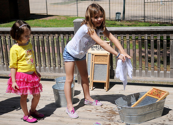 Sloan Turnbow (left) watches as her older sister, Cassidy (center) tries to stay dry while she washes a piece of laundry the old-fashion way at the Cherokee Strip Regional Heritage Center Family Fun Day in Humphrey Heritage Village Saturday, April 13, 2013. (Staff Photo by BONNIE VCULEK)