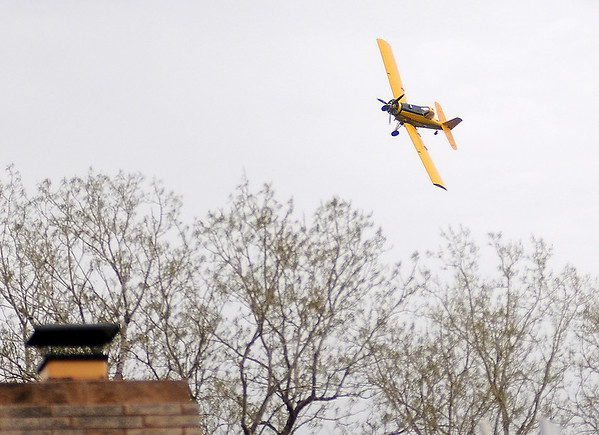 An aircraft flies over Hackberry Creek and a home northeast of Enid as the pilot sprays a field near Waukomis Friday, April 26, 2013. (Staff Photo by BONNIE VCULEK)