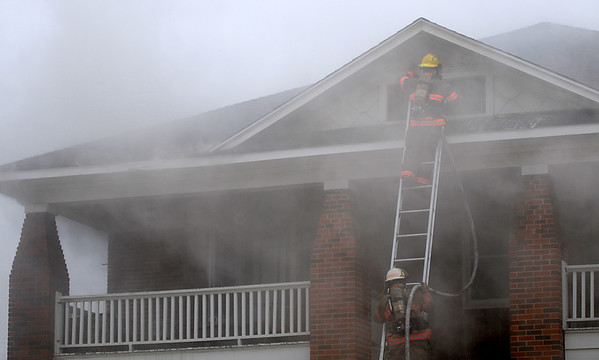 Enid firefighters extinguish a blaze at 412 W. Pine after a fire inside a garage quickly spread to the residence and caused damage to an adjacent home Wednesday, April 17, 2013. (Staff Photo by BONNIE VCULEK)
