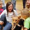 Scooter, a former rescue dog from the Enid SPCA sits among members of Girl Scout Troop 211 at Chisholm Elementary Monday. The troop raised $1,000 that they donated to the Enid SPCA. (Staff Photo by BILLY HEFTON)
