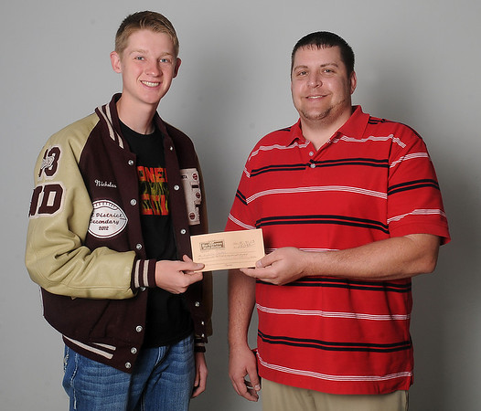 Nicholas Denker (left) accepts a $150 gift certificate to Big Country Meat Market from James Cross at Enid News & Eagle Wednesday, April 10, 2013. Denker, a senior at Pioneer High School, was the NCAA Women's Basketball bracket winner. (Staff Photo by BONNIE VCULEK)