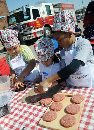 Smokin' Grillaz (from left) Selena Jacobo, Priscilla Jacobo and Nikolas Pennewell use a hamburger press as they prepare two pounds of meat for seasoning during the 1st annual Kids-Q at the 8th annual Roberts Ranch Smokin' Red Dirt BBQ west of Convention Hall Friday, April 19, 2013. (Staff Photo by BONNIE VCULEK)
