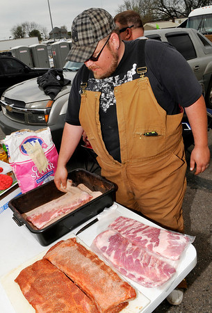 Jesse Pye of the 3 Chubs & a Rub BBQ team applies a dry rub to slabs of ribs Saturday during the Smokin' Red Dirt Barbeque contest in downtown Enid. (Staff Photo by BILLY HEFTON)