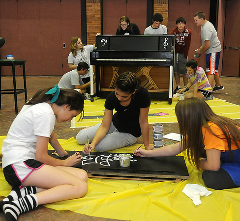 Advanced Art design team members (front, from left) Kendall Carpenter, Alana Brehm and Jesse Elledge complete music symbols on the front panel of a piano as fellow students in Pam Gilbreath's class from Waller Middle School finish the primer and base coat on the back and sides of their Tri-State art project, sponsored by Main Street Enid. (Staff Photo by BONNIE VCULEK)