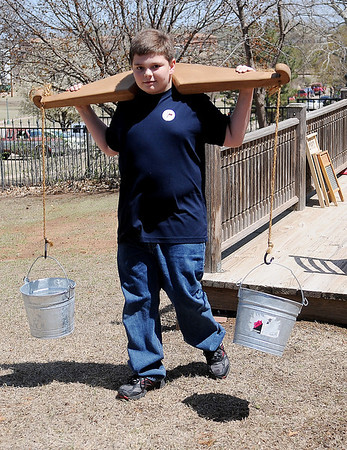 Callum Wright fetches fresh water for the laundry during the Cherokee Strip Regional Heritage family fun day in Humphrey Heritage Village Saturday, April 13, 2013. (Staff Photo by BONNIE VCULEK)