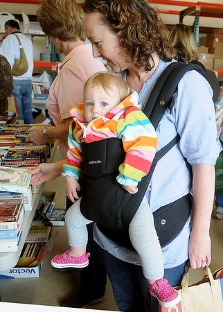 Little Martha White has a comfortable seat as her mother, Lisa, searches for novels at the Hospice Circle of Love spring book sale Friday, April 12. Lisa White has taken her daughter to the sale each year since her birth. The book sale continues tomorrow from 9 a.m.-1 p.m. and all proceeds from the sale benefit Hospice Circle of Love clients. (Staff Photo by BONNIE VCULEK)