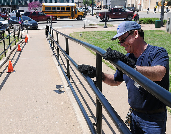 United States Postal Service maintenance employee Christopher Grellner uses mitts to paint the handicap rails outside the Enid post office Wednesday, April 24, 2013. (Staff Photo by BONNIE VCULEK)