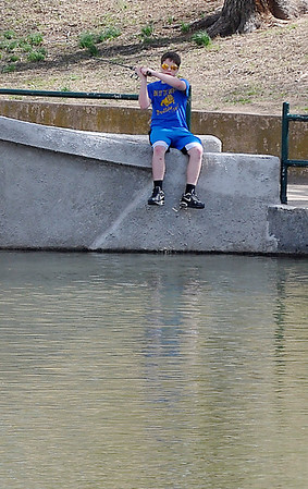 A boy cast a line from the bridge at Governments Springs Park Sunday. (Staff Photo by BILLY HEFTON)