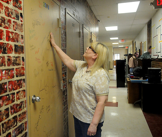 Connie Hood, a teacher at Lincoln Alternative School, reads names of several of her former students as workers prepare the school's top floor for renovations Friday, April 26, 2013. Wall of Fame signatures, student hand prints, special messages, artistic paintings by teachers and students will soon be destroyed during construction. Photographs of the memorabilia have been taken by Enid Public School officials and archived for use. (Staff Photo by BONNIE VCULEK)